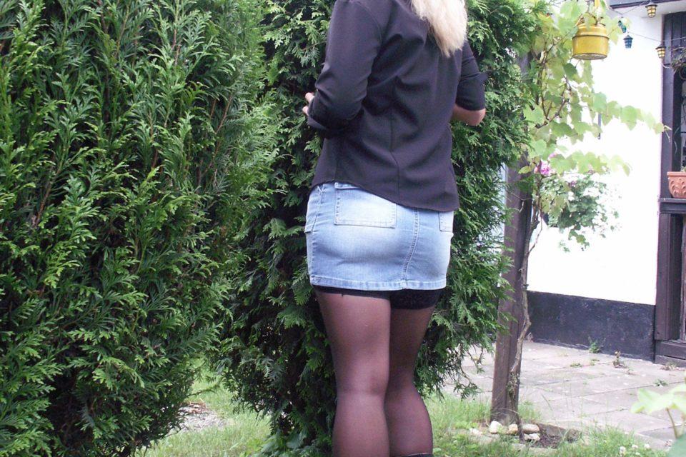 Blondine im Minirock im Garten